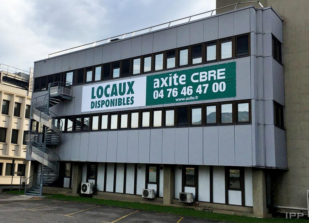 Banderole avec œillets fixée sur façade pour AXITE CBRE